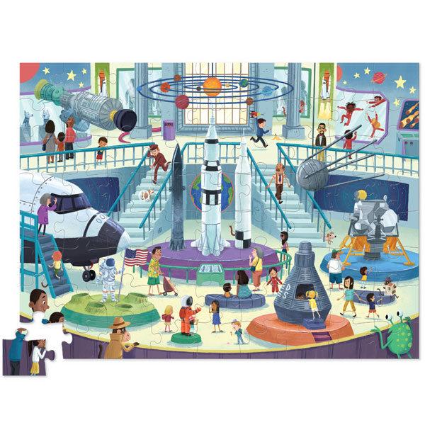 """Crocodile Creek Day at the museum space puzzel 72 stuks vanaf 5j De Day at the museumspace puzzel is een educatieve puzzel voor kinderen vanaf 5 jaar. In de mooie 10cm x 23cm ronde doos zitten 72 stevige kartonnen puzzelstukken. Ontdek al spelenderwijs in het museum de verschillende soorten ruimtevoertuigen. De afmeting van """"de dag in het museum space puzzel"""" is 35cm x 48cm. De mooie puzzel is geschikt voor kinderen vanaf 5 jaar. De prachtige puzzels zijn ontworpen in New York door het Amerikaanse merk Crocodile Creek. De puzzel en de verpakking zijn gemaakt van 100% gerecycled karton en gedrukt met inkt op soja basis en watergedragen lak. Ontdek ook uit dezelfde """"Day at the museum"""" collectie de dinosaurus en aquarium puzzels met 72 puzzelstukken."""