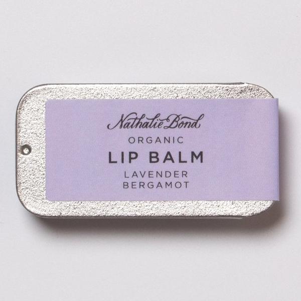 Nathalie Bond Lippenbalsem Lavendel & Bergamot Nathalie Bond-lippenbalsems zijn gemaakt met de beste biologische, veganistische, duurzaam geproduceerde ingrediënten om uw huid te kalmeren, hydrateren en beschermen. Gemaakt met biologische en natuurlijke ingrediënten. + 100% natuurlijk + 77% biologisch + Cacaoboter is diep hydraterend en rijk aan voedingsstoffen die helpen om uitdroging te verminderen en de flexibiliteit van de huid te verbeteren. Het biedt ook een goede beschermlaag tegen barre weersomstandigheden. + Calendula-olie staat bekend om zijn kalmerende en verzachtende eigenschappen op de huid en helpt overtollige olie te bestrijden. Bevat vitamine A, vitamine B1, vitamine B2, vitamine B6, vitamine E en salicylzuur. + Olijfolie is een zware, vette olie die erg voedzaam is en geweldig voor de droge en schrale huid. Breng een kleine hoeveelheid aan op de vingertoppen en strijk gelijkmatig over de lippen. Ontdek ook de biologischezeep en vloeibare zeep met Lavendel en Bergamot van Nathalie Bond.