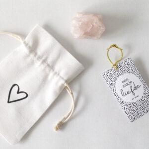 Een zakje liefde met een rozenkwarts edelsteen Dit zakje van By Romi gemaakt van katoen is gevuld met een rozenkwarts edelsteen. Rozenkwarts is traditioneel de steen van de liefde. Niet alleen romantische liefde, maar ook liefde voor familie en vrienden en liefde voor jezelf. Het trekt liefde aan, helpt je om lief te hebben en om je open te stellen voor het ontvangen van liefde. Als rozenkwarts in een ruimte geplaatst wordt, brengt het liefde, harmonie en rust. Afmeting zakje: 7,5 x 13 cm Afmeting Rozenkwarts edelsteen: 3/4 cm